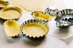 Preparing pies with pastry. Preparing pastry patties on aluminum molds Royalty Free Stock Photography