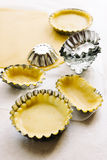 Preparing pies with pastry. Preparing pastry patties on aluminum molds Stock Photography