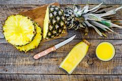 Preparing pineapple juice. Bottle with beverage near fruit slices and knife on wooden background top view Stock Photography