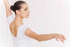 Preparing for pirouette. Beautiful young ballerina in white tutu dancing in ballet studio Stock Photo
