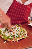 Preparing Pizza. Man spreading cheese over pizza Royalty Free Stock Images