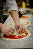 Preparing of pizza at kitchen of italian pizzeria. Royalty Free Stock Photos
