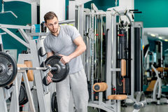 Preparing for power exercises. Young and handsome athletic man l Royalty Free Stock Photo