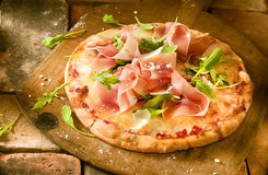 Preparing a proscuitto and rocket pizza Stock Photo