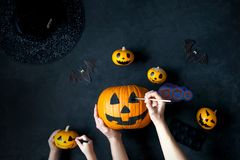 Preparing pumpkin for Halloween. A mom with a child draw faces on the pumpkins Stock Photo