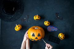 Preparing pumpkin for Halloween. A mom with a child draw faces on the pumpkins Stock Image