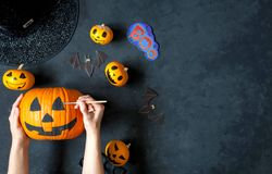 Preparing pumpkin for Halloween. A mom with a child draw faces on the pumpkins Stock Photos
