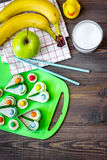 Preparing quick lunch for schoolchild. Funny sandwiches, milk, fruits on dark wooden table background top view copyspace Stock Photo