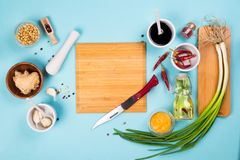 Preparing radish kimchi. Korean traditional cuisine. Ingredients for cooking a famous Korean dish kimchi from radish with a wooden plate in the middle with a Royalty Free Stock Image