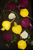 Preparing raw beetroots and garlic for roasting on a baking tray Royalty Free Stock Photos
