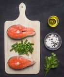 Preparing raw salmon steak with herbs, salt, pepper and other seasonings, two steaks lie on  cutting board, on a black backgrou. Preparing raw salmon steak with Stock Image