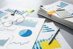 Preparing report. Blue graphs, glasses, calculator and pen. Royalty Free Stock Image
