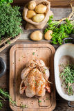 Preparing roast chicken with herbs and vegetables Stock Photo