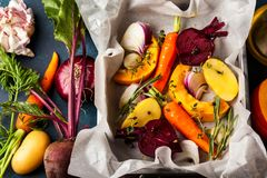 Oven Roasted vegetables. Preparing  roasted vegetables with garlic and herbs on the baking tray. Autumn-winter root vegetables Stock Photos