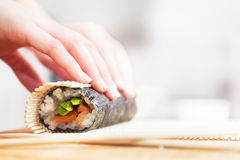 Preparing, rolling sushi. Salmon, avocado, rice and chopsticks on wooden table. Royalty Free Stock Image