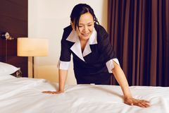 Attentive foreign hotel staff making bed. Preparing room. Smiling woman leaning on left arm and expressing positivity while working at hotel royalty free stock image