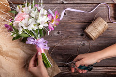 Preparing a rustic bouquet from gillyflowers and alstroemeria on Royalty Free Stock Image