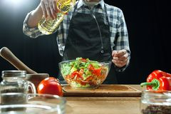 Preparing salad. Female chef cutting fresh vegetables. Cooking process. Selective focus royalty free stock photography