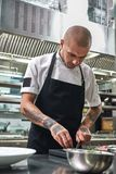 Preparing a salad. Handsome chef with tattoos on his arms cutting cucumber and other food ingredients while standing in. Kitchen royalty free stock photography
