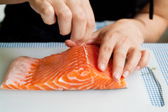 Preparing salmon. A chef removing bones from a piece of salmon for cooking Royalty Free Stock Image