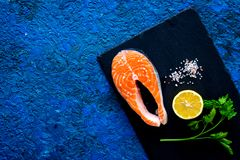 Preparing salmon steak with spices, seasoning. Piece of fresh fish on cutting board near salt, lemon slices, greenery on. Preparing salmon steak with spices Royalty Free Stock Photo