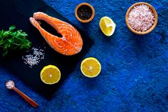 Preparing salmon steak with spices, seasoning. Piece of fresh fish on cutting board near sea salt, lemon slices. Preparing salmon steak with spices, seasoning Royalty Free Stock Images