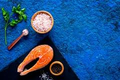 Preparing salmon steak with spices, seasoning. Piece of fresh fish on cutting board near sea salt, lemon slices. Preparing salmon steak with spices, seasoning Royalty Free Stock Photos