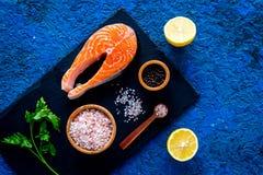 Preparing salmon steak with spices, seasoning. Piece of fresh fish on cutting board near sea salt, lemon slices. Preparing salmon steak with spices, seasoning Royalty Free Stock Photography