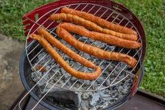 Preparing Sausage on Grill Stock Photos