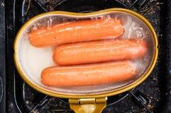 Preparing sausages in camping stock image