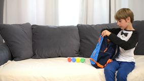 Preparing for school. Cute boy preparing backpack for first day of school stock video footage