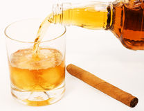 Preparing of scotch. Bottle pouring whiskey into the glass with ice cube, and cigar royalty free stock image