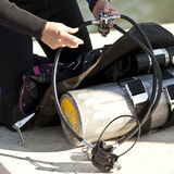 Preparing scuba gear for use. Detail of hands preparing scuba gear for use Royalty Free Stock Image