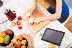 Preparing smoothie while getting online information about nutrit Royalty Free Stock Image