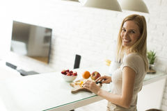 Preparing smoothies. Young woman preparing smoothie in the kitchen Royalty Free Stock Images