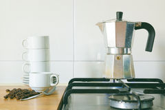 Preparing some coffee with a kettle on a burner of a rustic kitchen, next to a pile of cups and some grains. Empty copy space for Editor`s text Royalty Free Stock Photos