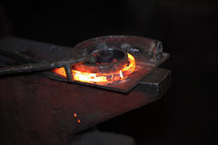 Preparing  some figure from hot steel stick. On the anvil with special tool Stock Photo