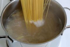 Preparing spaghetti pasta meal: cooking noodles in water Royalty Free Stock Photography