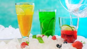 Preparing Summer Spritzer drinks with fresh fruit with sparkling mineral water. Preparing Summertime Spritzer drinks with fresh fruit, mango, berries, cucumbers Royalty Free Stock Photos
