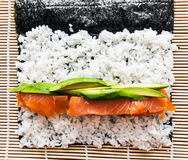 Preparing sushi background. Salmon, avocado, rice on seaweed. Stock Image
