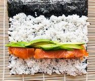 Preparing sushi background. Salmon, avocado, rice on seaweed. Stock Image