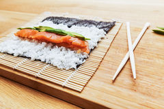 Preparing sushi. Salmon, avocado, rice and chopsticks on wooden table. Stock Photos