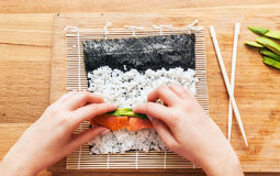 Preparing sushi. Salmon, avocado, rice and chopsticks on wooden table. Royalty Free Stock Photos