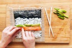Preparing sushi. Salmon, avocado, rice and chopsticks on wooden table. Royalty Free Stock Photo