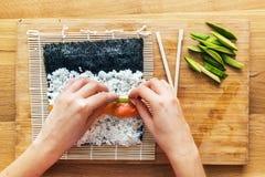Preparing sushi. Salmon, avocado, rice and chopsticks on wooden table. Stock Photo