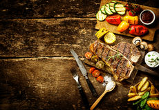 Preparing t-bone steak and roast vegetables. In a country kitchen with bell peppers, mushrooms, tomato, potato, mangetout peas, and corn on a rustic wooden Stock Photos