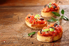 Preparing tasty Italian bruschetta. With chopped vegetables and oil on grilled or toasted crusty baguette sprinkled with seasoning and spices on an old grungy Stock Image