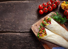 Preparing tasty Tex-Mex tortilla wraps. In a rustic kitchen filled with fresh salad ingredients, corn kernels, herbs and diced meat , overhead view with stock images