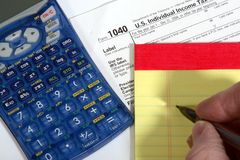 Preparing taxes. Hand and pencil with pad, calculator and tax form Stock Photos