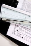Preparing Taxes - Check and Forms on Keyboard Stock Photo